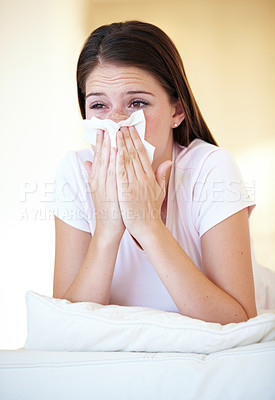 Buy stock photo A gorgeous young woman blowing her nose while lying on her bed
