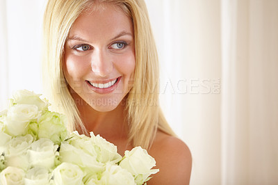 Buy stock photo An attractive young woman holding a bouquet of flowers while looking away