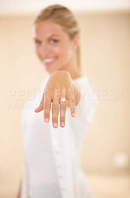 Buy stock photo Portrait of a beautiful young woman showing off her engagement ring