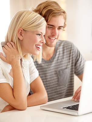 Buy stock photo A young couple using a laptop to browse the web