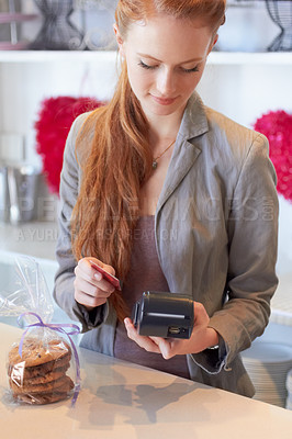 Buy stock photo An attractive young woman swiping your card in her bakery