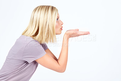 Buy stock photo Pretty young woman blowing a kiss while isolated on white