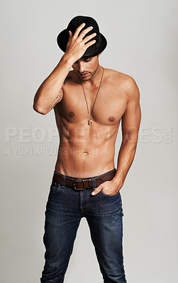 Buy stock photo A muscular young man standing shirtless while holding a hat on his head