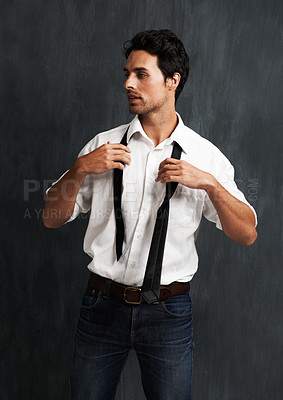 Buy stock photo A handsome young man getting dressed