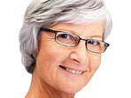Closeup of senior retired woman smiling on white background