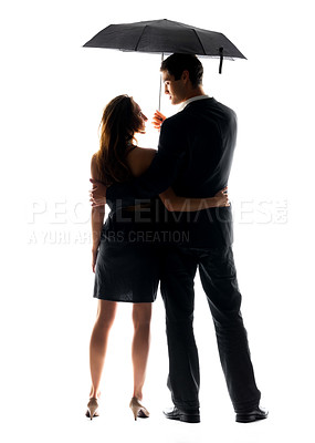 Buy stock photo Rear view of a happy young couple standing under umbrella against white background
