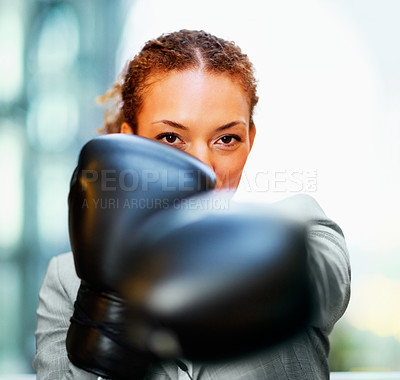 Buy stock photo African American business woman in a fighting position at work wearing boxing gloves