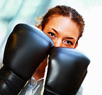 Business woman with her face covered by boxing gloves