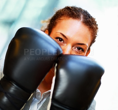 Buy stock photo Young African American business woman covering her face with boxing gloves