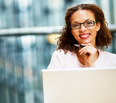 Buy stock photo Portrait of a happy African American business woman wearing spectacles working on a laptop