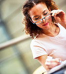 Cute young business woman making a note, looking through her specs