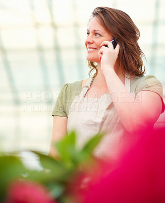 Buy stock photo Happy young female florist speaking on the cellphone while at a greenhouse, looking away