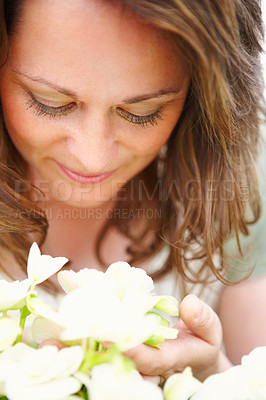 Buy stock photo Close up portrait of a pretty woman looking at  white spring flowers outdoors