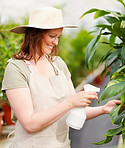 Young lady wearing a hat watering the plants