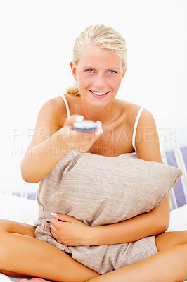 Buy stock photo Portrait of happy young woman holding a television remote control