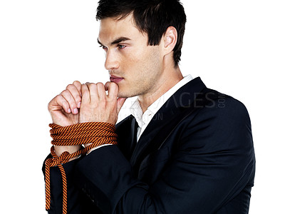 Buy stock photo Portrait of a thoughtful young male executive being tied with a rope  against white background