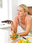 Middle aged woman with the TV remote while preparing dinner in t