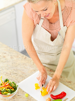 Buy stock photo Top view of a happy mature woman cutting vegetables for a salad