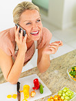 Mature woman speaking on the mobile phone , preparing a salad