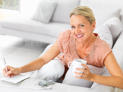 Buy stock photo Happy mature female seeking for jobs in newspaper while having cup of coffee