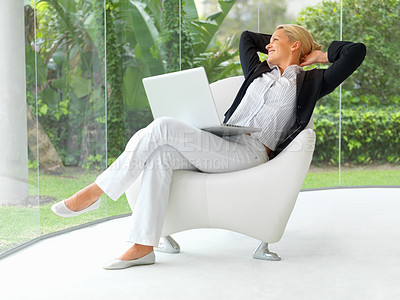 Buy stock photo Portrait of mature business woman sitting with a laptop, looking outside through glass wall