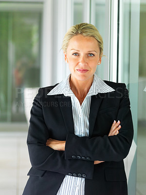 Buy stock photo A confident middle age business woman in black suit standing with hands folded