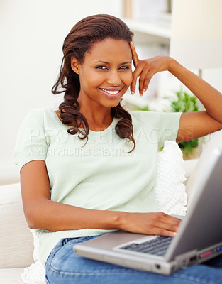 Buy stock photo Happy African American young woman using a laptop at home