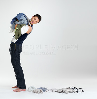 Buy stock photo Portrait of a handsome young male carrying clothes in laundry