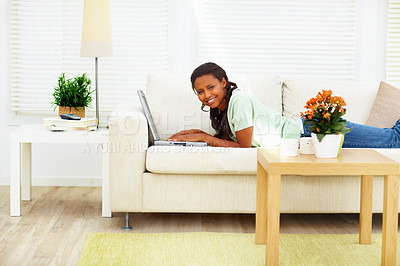 Buy stock photo An African American young woman lying on sofa and using laptop
