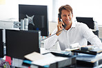Businessman speaking on phone at office desk