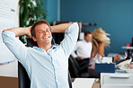 Happy corporate businessman relaxing at desk