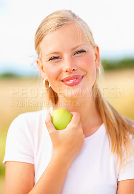 Buy stock photo Cute smiling young female having an apple outdoors