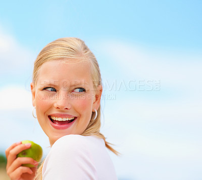 Buy stock photo Pretty young female eating a green apple while out in the meadow
