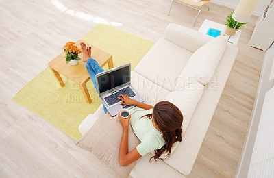 Buy stock photo Top view of a young African American girl on sofa drinking tea while using a laptop