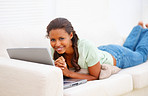 An African American female lying on couch and using laptop