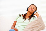 Young African American woman listening to music on headphones at