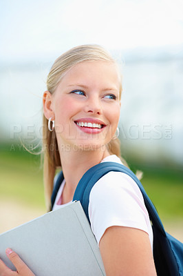 Buy stock photo Sweet young college student holding a folder and smiling outdoors