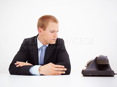 Buy stock photo Young businessman at the desk in the office waiting for a call