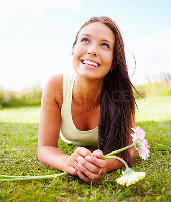 Buy stock photo Happy young female lying at the park, looking upwards