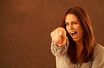 Pretty excited young woman pointing at you against brown background