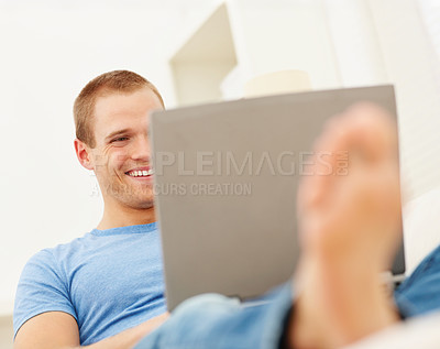 Buy stock photo Happy young boy working on a laptop while relaxing at home