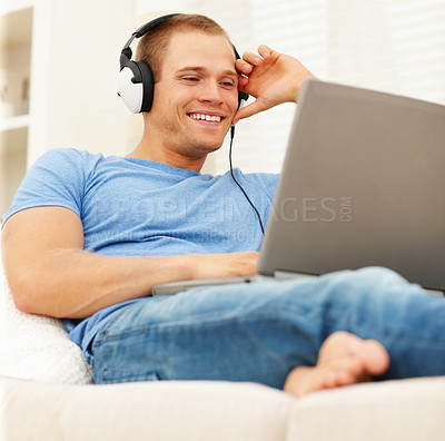 Buy stock photo Handsome young guy relaxing at home listening to music from the internet
