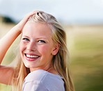 Sweet young female playing with hair, smiling outdoors