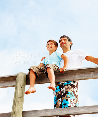 Buy stock photo Father and son relaxing under a clouded sky, boy sitting on the wooden railing