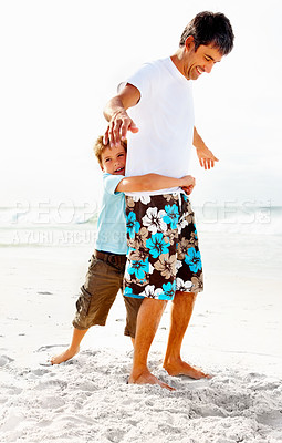 Buy stock photo Full length of a little boy at the beach with his arms around his father