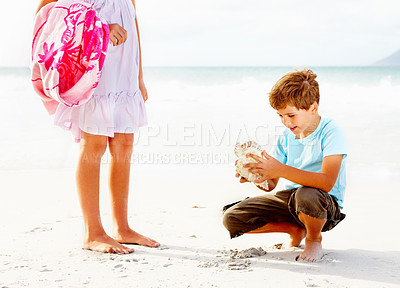 Buy stock photo Brother and sister at the sea shore, happy boy playing with a sea shell