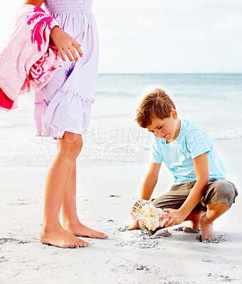 Buy stock photo Brother and sister at the sea shore, happy boy holding with an abandoned sea shell