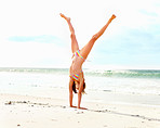 A girl on a beach doing a cartwheel