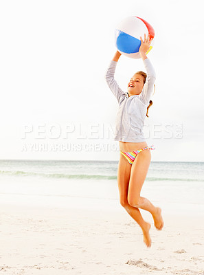 Buy stock photo Happy young girl in a bikini playing with a ball, jumping in the air