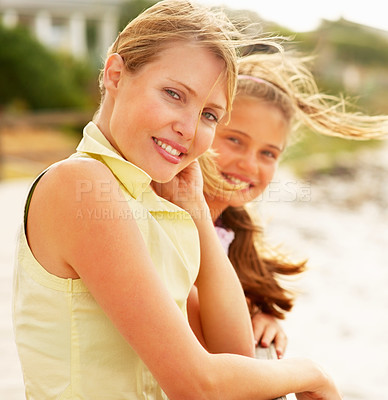 Buy stock photo Lovely mature female at the beach with her teenage daughter at the back